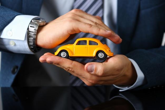 양복과 넥타이에 남성 팔 커버 노란색 장난감 자동차