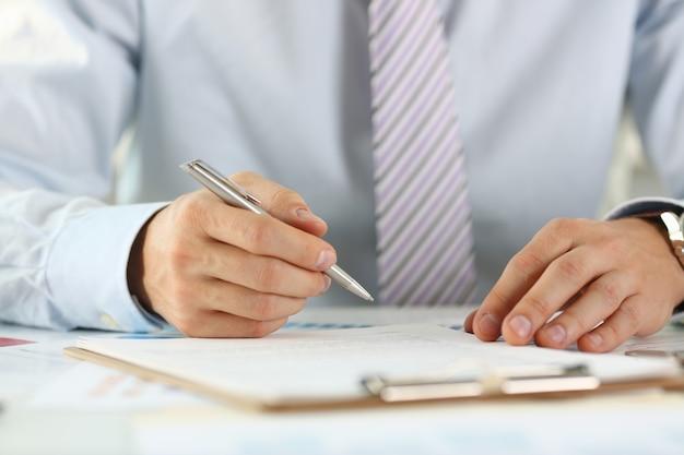スーツとネクタイの男性の腕は銀のペンを保持します