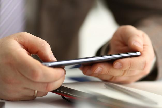 スーツの男性の腕は電話と銀のペンを保持します