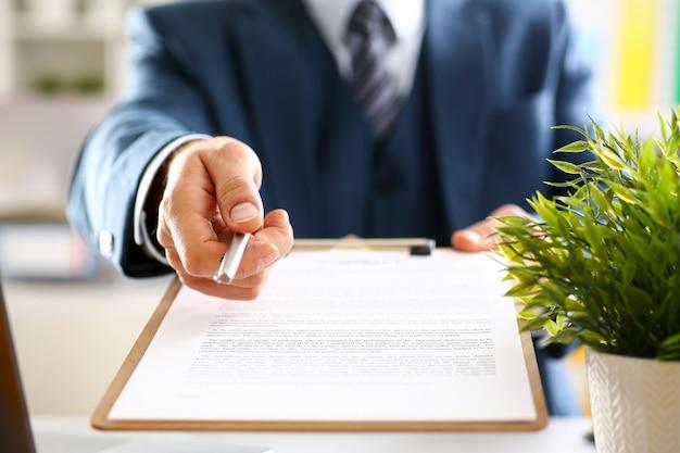 Мужская рука в костюме предлагает форму контракта в буфер обмена