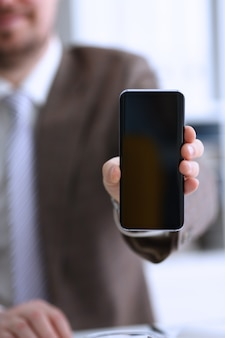 カメラ付き携帯電話のディスプレイにスーツショーの男性の腕
