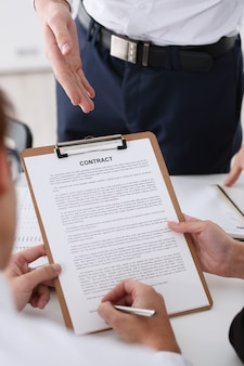Male arm in shirt offer contract form on clipboard pad and silver pen to sign closeup. strike a bargain for profit white collar motivation union decision corporate sale insurance agent concept