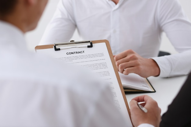 Male arm in shirt offer contract form on clipboard