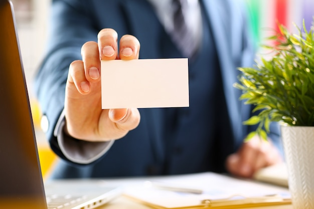 Male arm in suit give blank business card to visitor closeup.