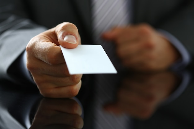 Male arm in suit give blank calling card to visitor closeup