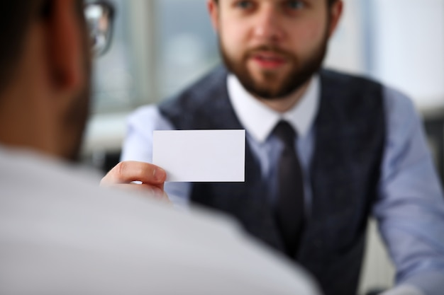 Male arm in suit give blank calling card to visitor