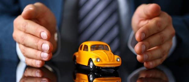 Male arm in suit and tie cover yellow toy car