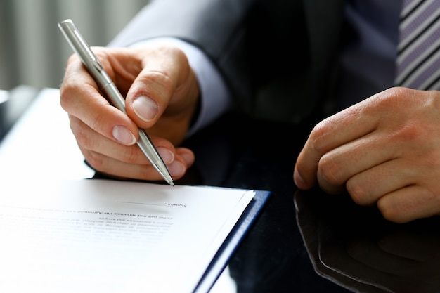 Male arm in suit and tie fill form clipped to pad with