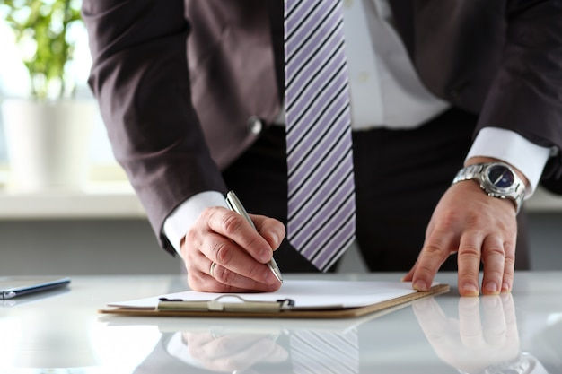 Male arm in suit and tie fill form clipped to pad