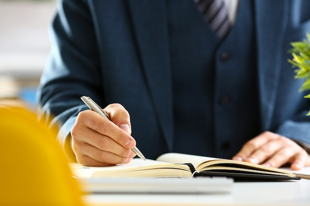 Male arm in suit and tie hold silver pen filling schedule in notepad at office workplace closeup.