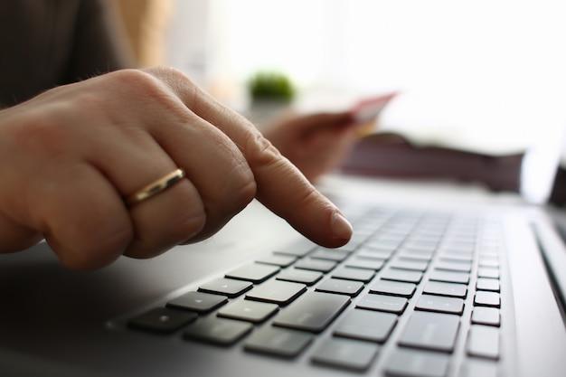 Мужские руки держат кнопки кредитной карты, делающие перевод