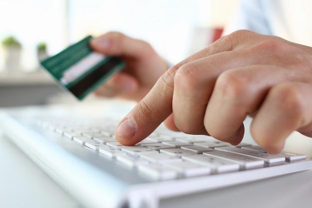 男性の腕はクレジットカードのプレスボタンを押したままにします