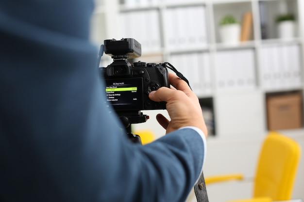 Мужские руки в костюме крепят видеокамеру к штативу