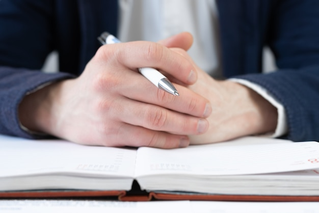 Male arms in suit holding pen closeup. cropped view of businessman works with financial papers at the table. finance concept