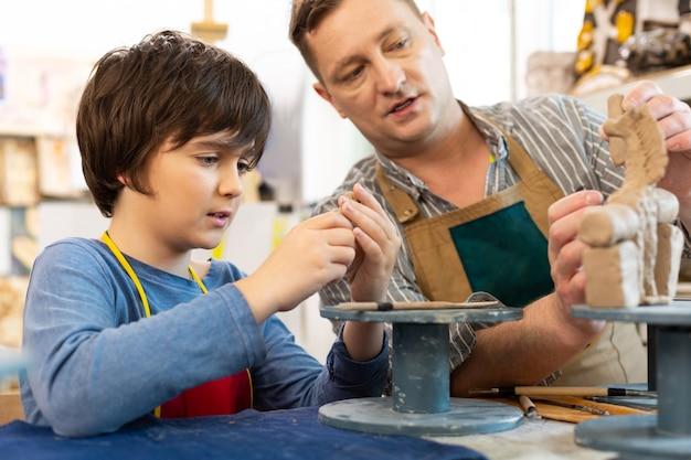 Учитель-мужчина разговаривает с учеником, давая урок о глине