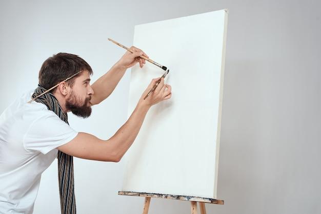 男性アーティストが首にイーゼルアートの趣味の軽いスカーフを手にブラシをかけます。