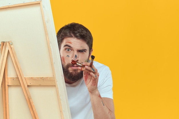 Художник-мужчина рисует на мольберте на желтом