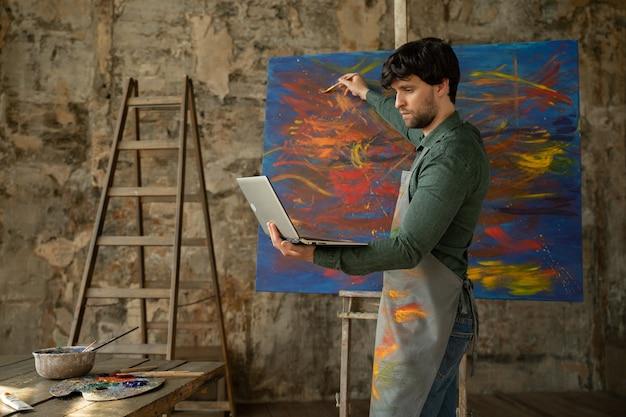 Художник-мужчина рисует картину и проводит дистанционное обучение рисованию. мужчина показывает, что она рисует и обучает своих учеников.