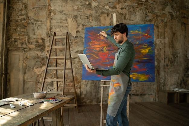 Художник-мужчина рисует картину и учится рисовать. мужчина учится рисовать онлайн через ноутбук.