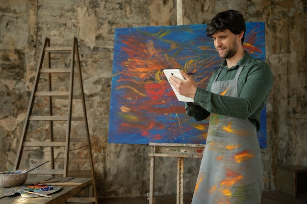 Male artist is standing in his studio and using a tablet working on a project workshop with oil painting