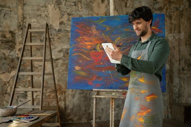 男性アーティストが彼のスタジオに立って、油絵のプロジェクトワークショップで作業しているタブレットを使用しています