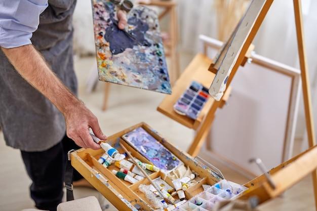 작업 과정에서 앞치마를 입은 남성 아티스트 남자, 붓을 사용하는 남성, 그림을위한 다양한 재료 페인트 도구
