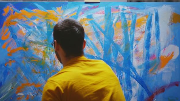 캔버스에 손으로 스튜디오에서 그림을 그리는 남성 예술가.