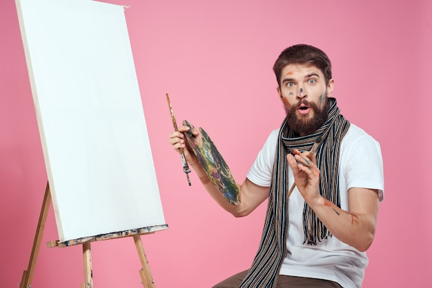 Художник-мужчина рисует картину на холсте с мольберта