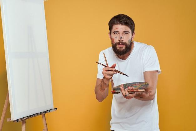 男性アーティストがキャンバスにイーゼルで絵を描く