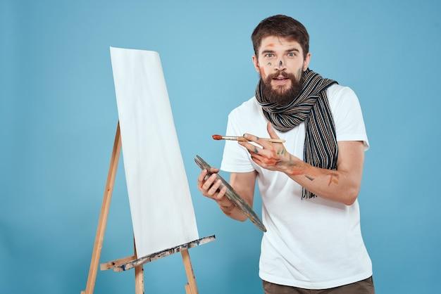 Художник-мужчина рисует на мольберте
