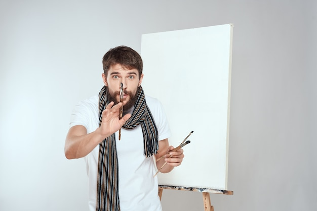 Male artist paints a picture on canvas with an easel