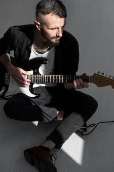Художник-мужчина играет на электрогитаре