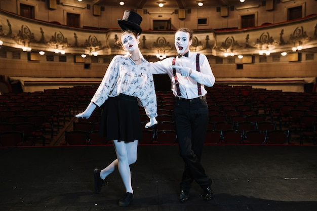 Male artist pointing finger at female mime artist standing on stage