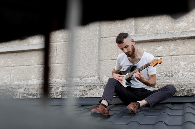 Male artist on roof top playing electric guitar