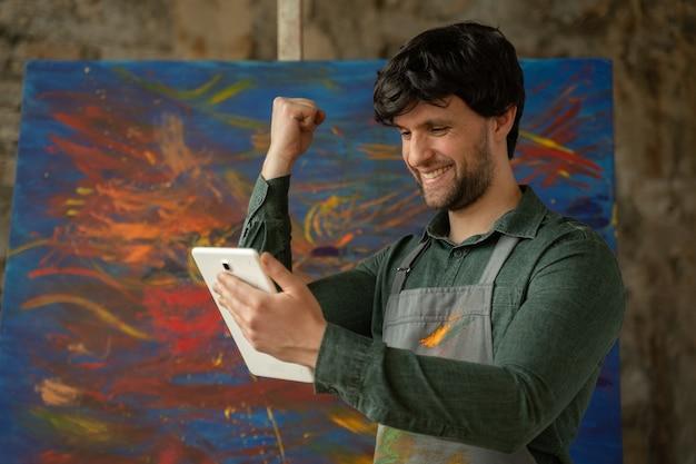 タブレットを使用して彼のスタジオに立っている男性アーティストが油絵でワークショップに勝つ