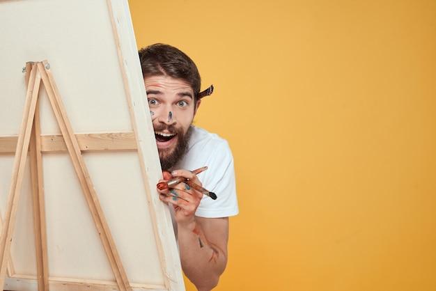 男性アーティストがイーゼルの感情の前に立ち、クリエイティブなアプローチを黄色に描きます。