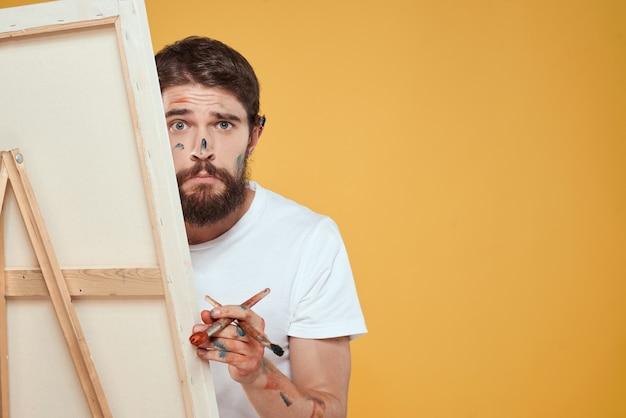 Художник-мужчина стоит перед мольбертом, рисующим эмоции