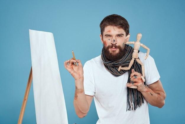 手で描く木製のダミーを持つ男性アーティスト