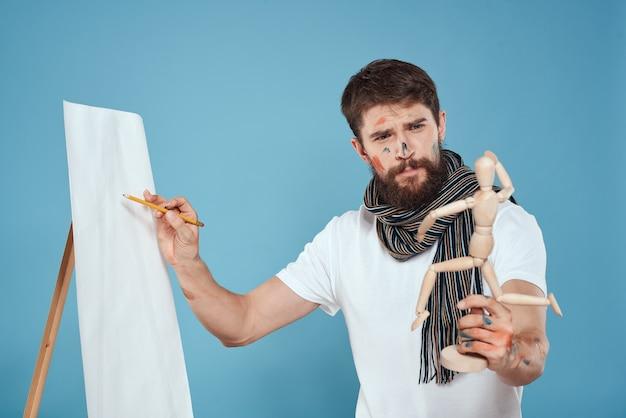 手に木製のダミーを持つ男性アーティスト