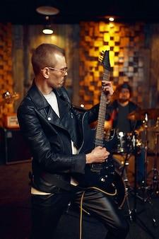 エレクトリックギターを持ち、ステージで音楽を演奏する男性アーティスト。ロックバンドの演奏またはガレージでの繰り返し、弦楽器を持った男、ライブサウンドパフォーマー