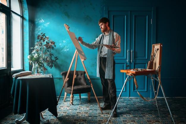 パレットと手でブラシを持つ男性アーティストは、窓の前のイーゼルにペイントします。