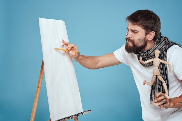 Male artist with a wooden dummy in hands drawing