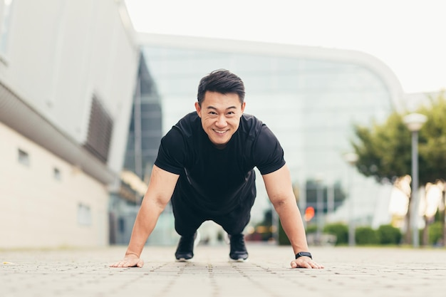 Male asian athlete doing fitness in the morning near the stadium pushes off the ground rejoices