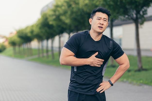 남자 아시아 운동선수, 공원에서 가슴 통증 피트니스가 있고 달리기, 심장 운동 후 심장 통증
