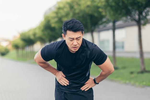 公園でのフィットネス後に腹痛を抱えている男性のアジアのアスリート