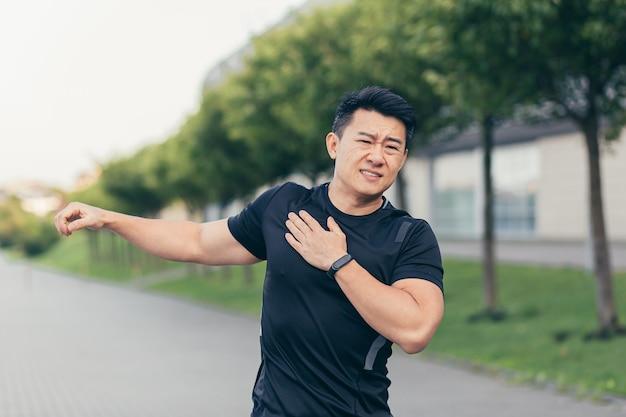 男性のアジアの運動選手、公園で肩の痛み、腕の筋肉の痛みをこねる