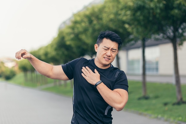 Male asian athlete, kneading shoulder pain, sore arm muscles in the park