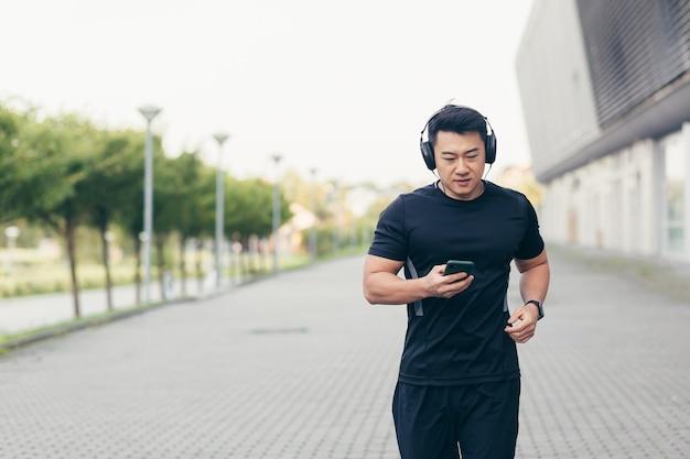 Азиатский спортсмен-мужчина на утренней пробежке в парке возле стадиона слушает музыку и подкаст в больших наушниках и использует телефон