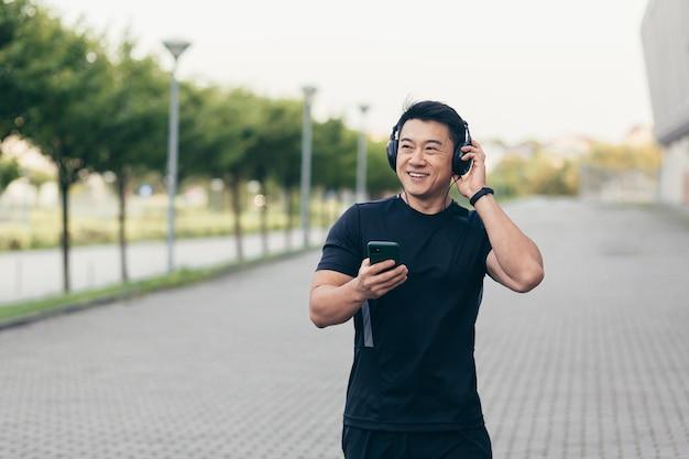 경기장 근처 공원에서 아침 달리기를 하는 남자 아시아 운동선수는 큰 헤드폰으로 음악을 듣고 팟캐스트를 사용합니다