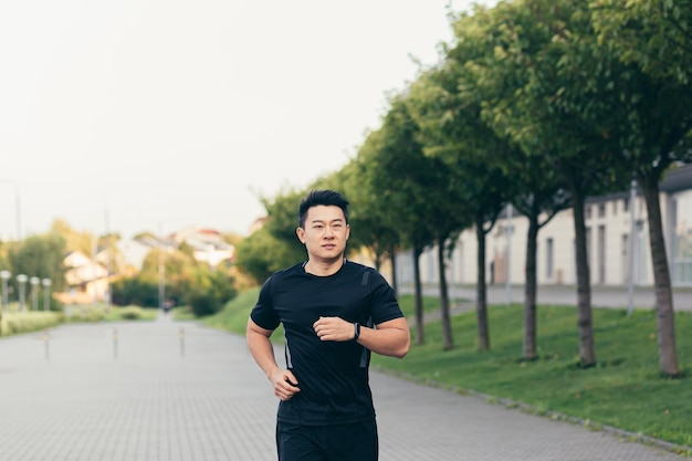 Азиатский спортсмен мужского пола на утренней пробежке в парке возле стадиона